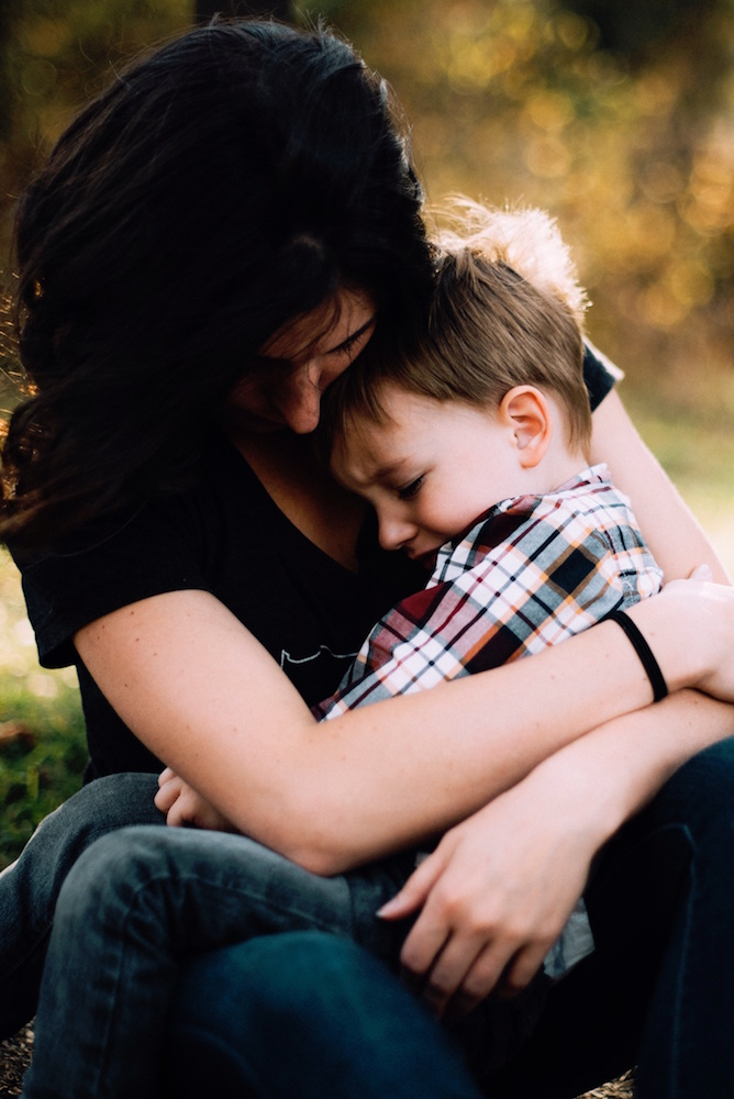 泣く子を抱く母