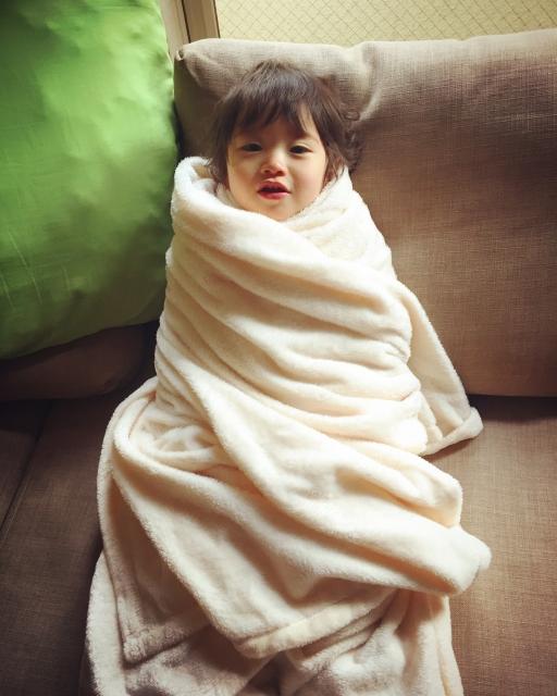 毛布でぐるぐるにされた子ども