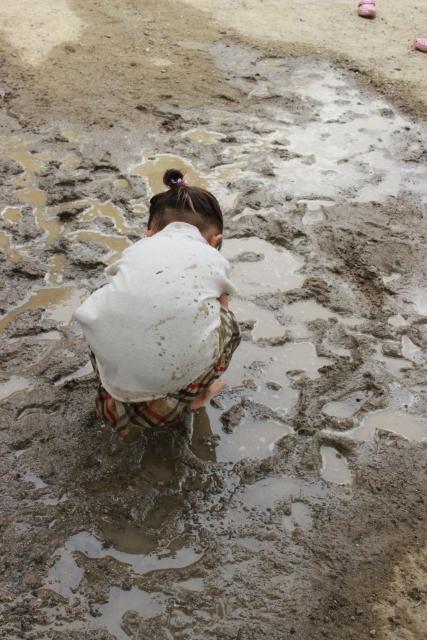 裸足で泥遊びする子ども